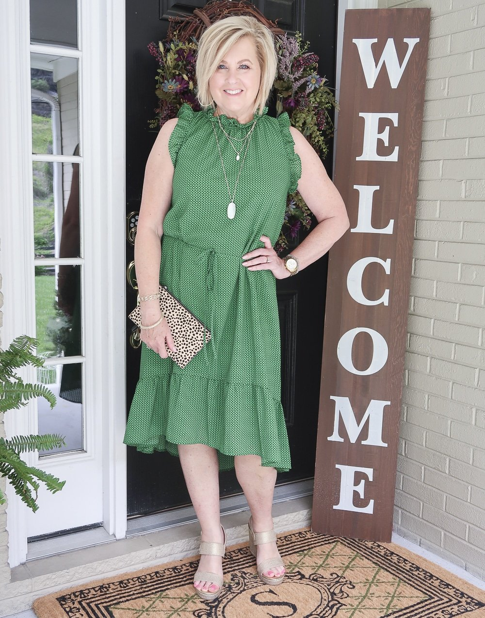 Fashion Blogger 50 Is Not Old is wearing a polka dotted dress that has a high neck and ruffles plus gold wedge shoes