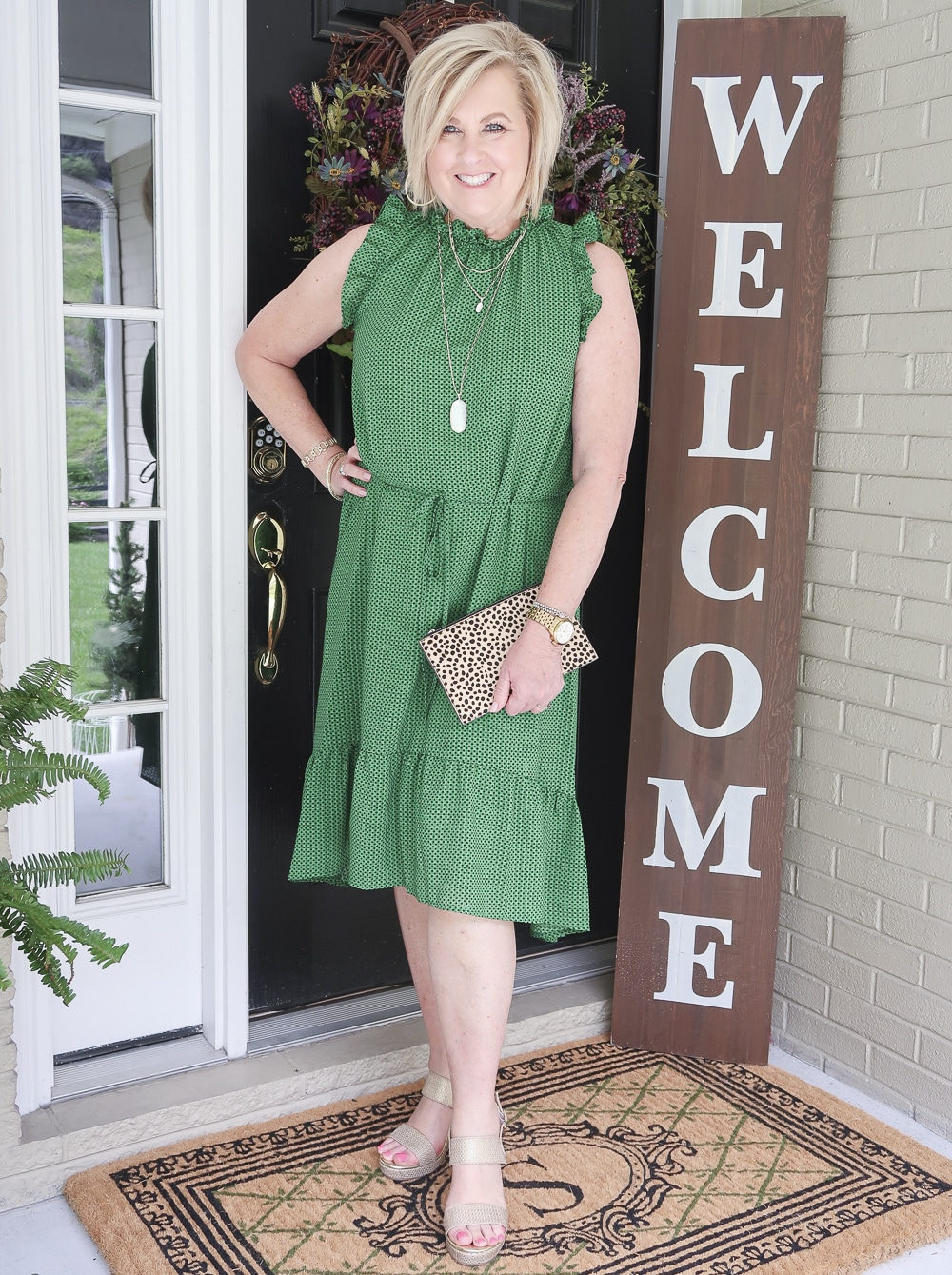 Fashion Blogger 50 Is Not Old is wearing a green polka dotted dress that has a high neck and ruffles plus gold wedge shoes
