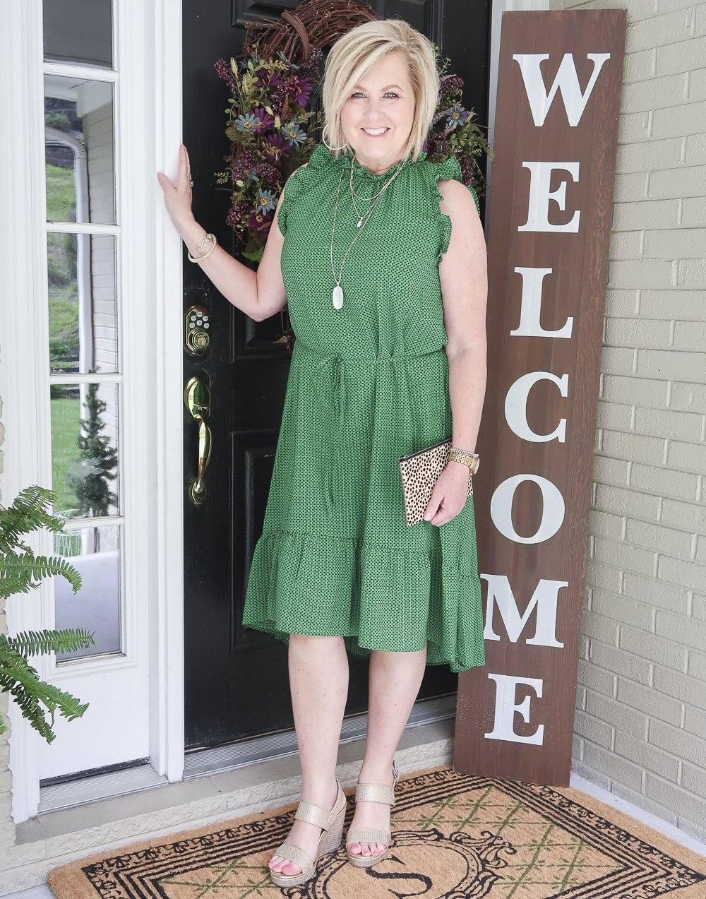 Fashion Blogger 50 Is Not Old is wearing a green polka dotted dress that has a high neck plus gold wedge shoes