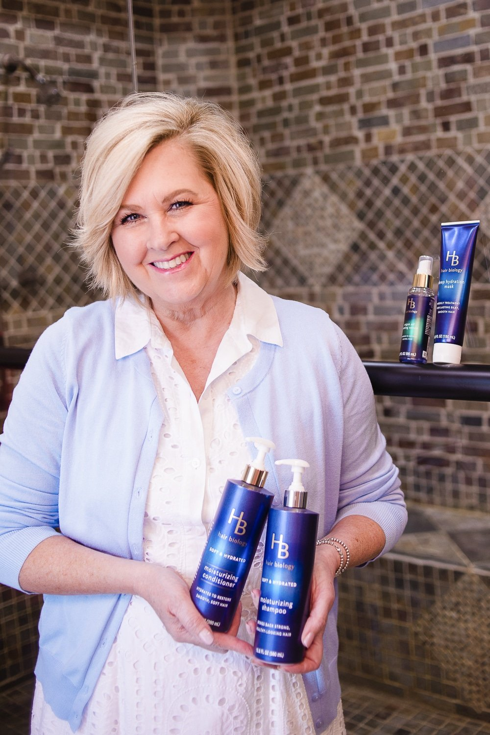 Fashion Blogger 50 Is Not Old holding shampoo and conditioner from Hair Biology