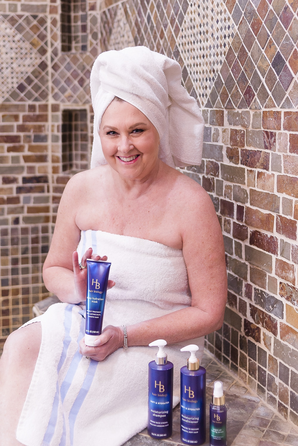 Fashion Blogger 50 Is Not Old with a towel on head holding hair products