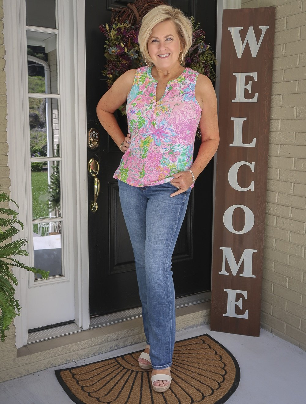 Fashion Blogger 50 Is Not Old is wearing a Lilly Pulitzer top with bootcut jeans and espadrille sandals