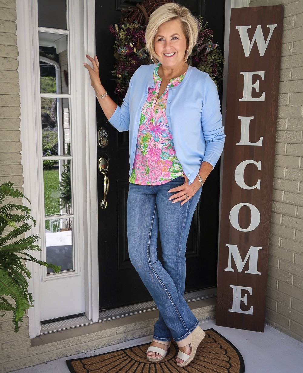 Fashion Blogger 50 Is Not Old is wearing a blue cardigan and a Lilly Pulitzer top with bootcut jeans