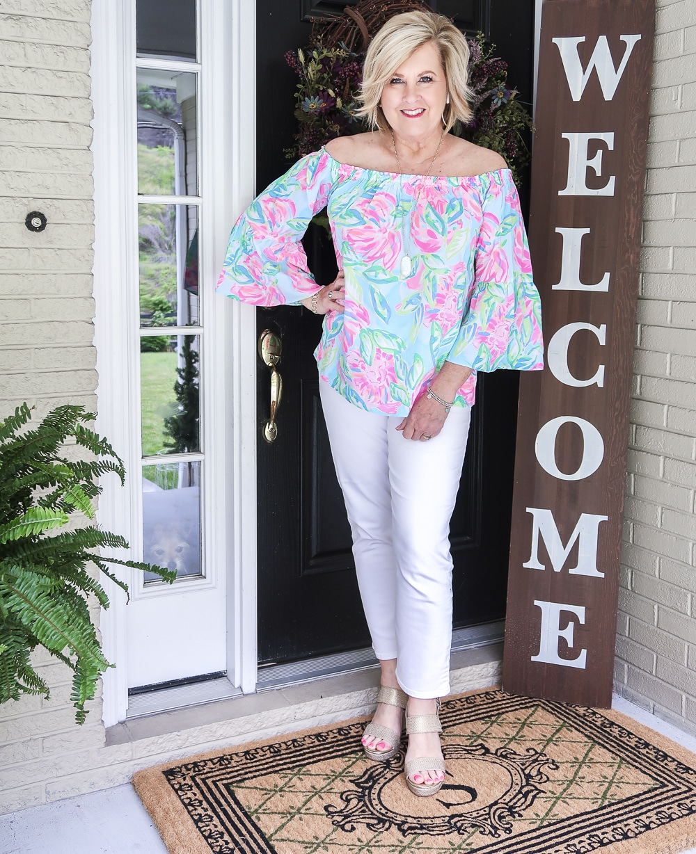 Fashion Blogger 50 Is Not Old wearing a colorful off the shoulder top from Lilly Pulitzer and white crop jeans with gold espadrilles