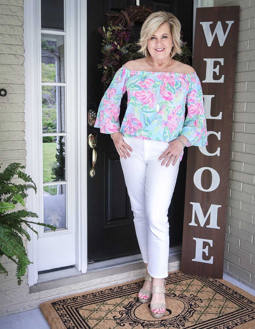 Fashion Blogger 50 Is Not Old wearing a colorful off the shoulder top from Lilly Pulitzer and white crop jeans with gold wedges
