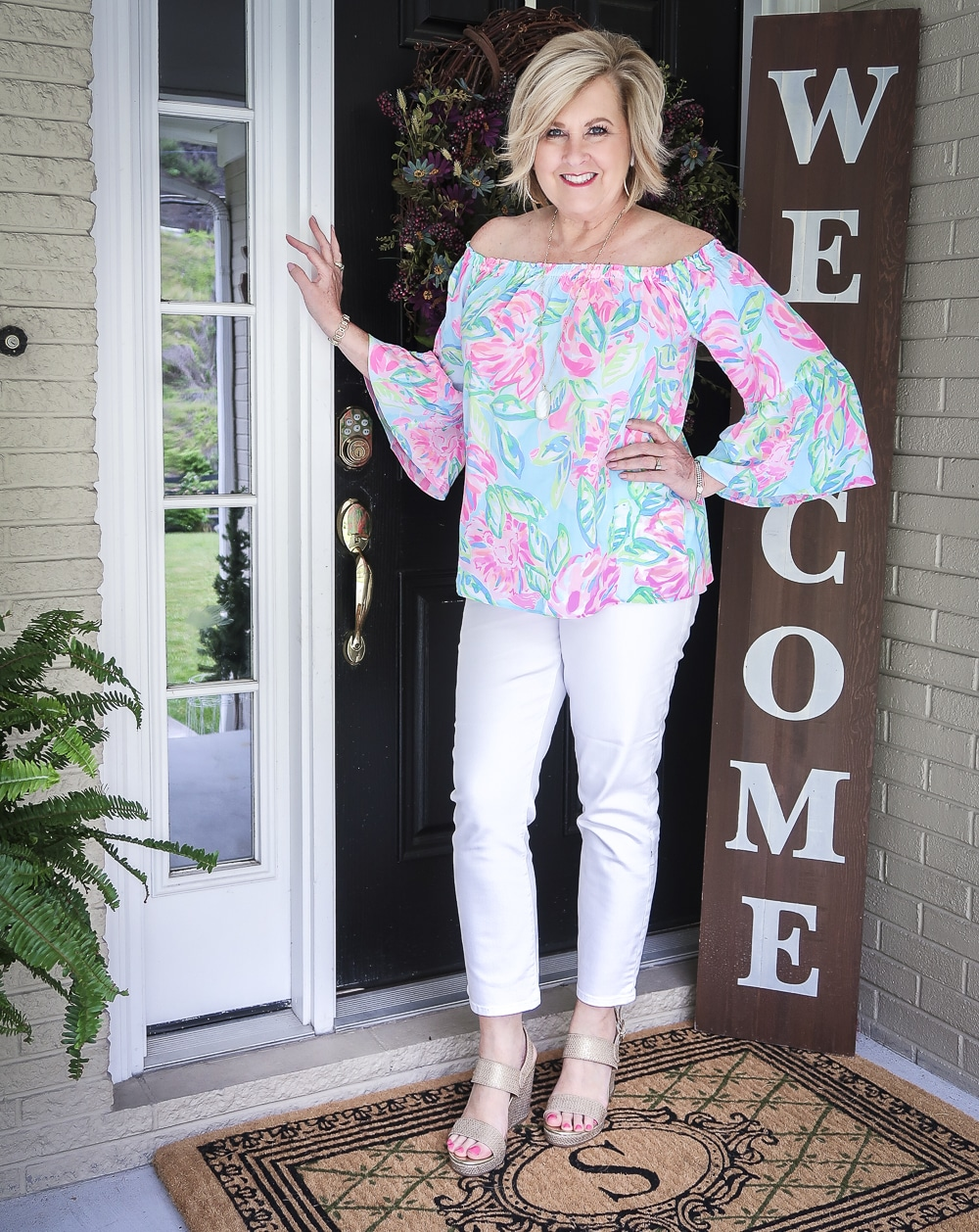 Fashion Blogger 50 Is Not Old wearing an off the shoulder top from Lilly Pulitzer and white crop jeans with gold espadrilles