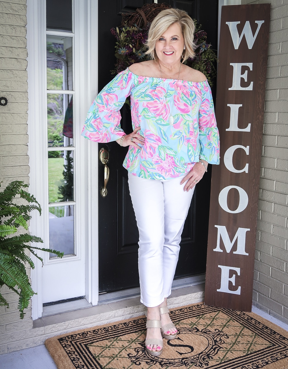 Fashion Blogger 50 Is Not Old wearing a colorful top from Lilly Pulitzer and white crop jeans with gold espadrilles