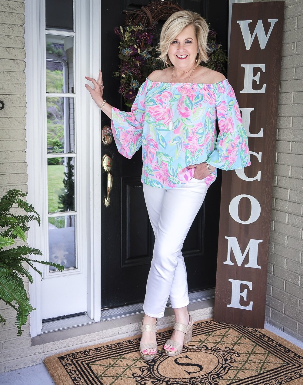 Fashion Blogger 50 Is Not Old wearing a colorful off the shoulder top from Lilly Pulitzer and white crop jeans