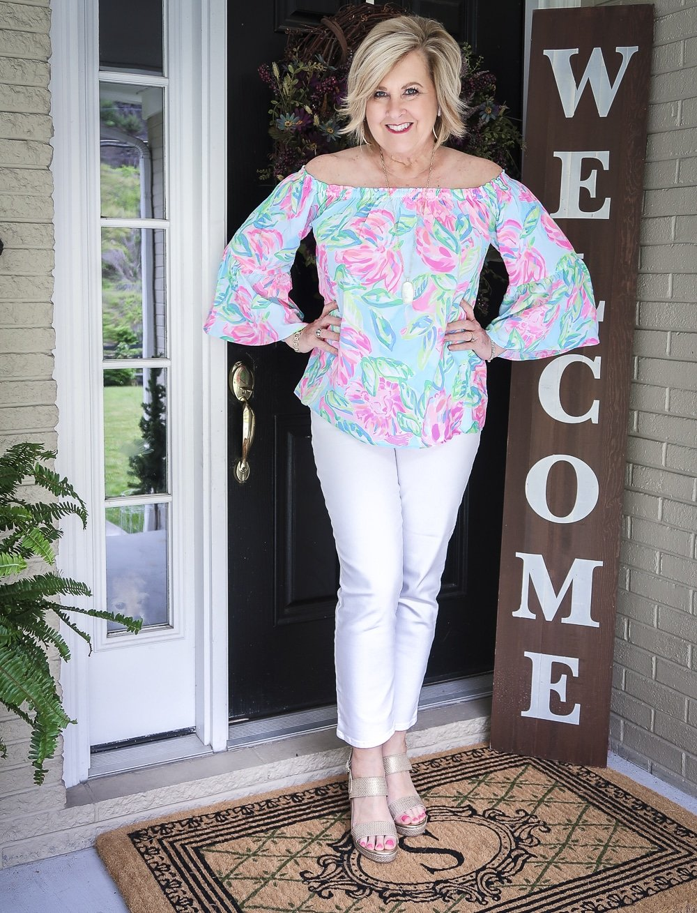 Fashion Blogger 50 Is Not Old wearing a colorful off the shoulder top from Lilly Pulitzer and white jeans with gold espadrilles