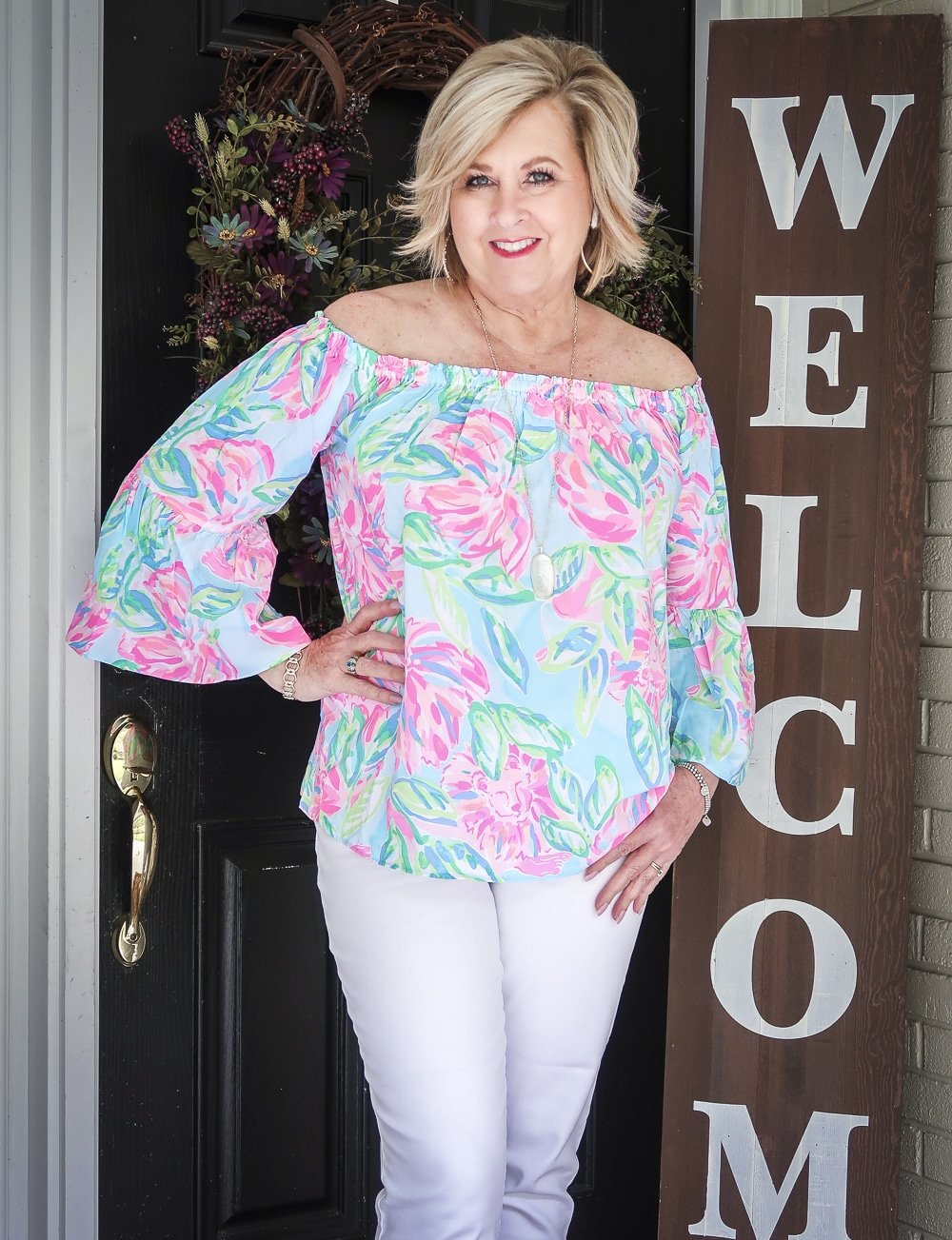 Fashion Blogger 50 Is Not Old wearing a colorful off the shoulder top from Lilly Pulitzer and gold jewelry