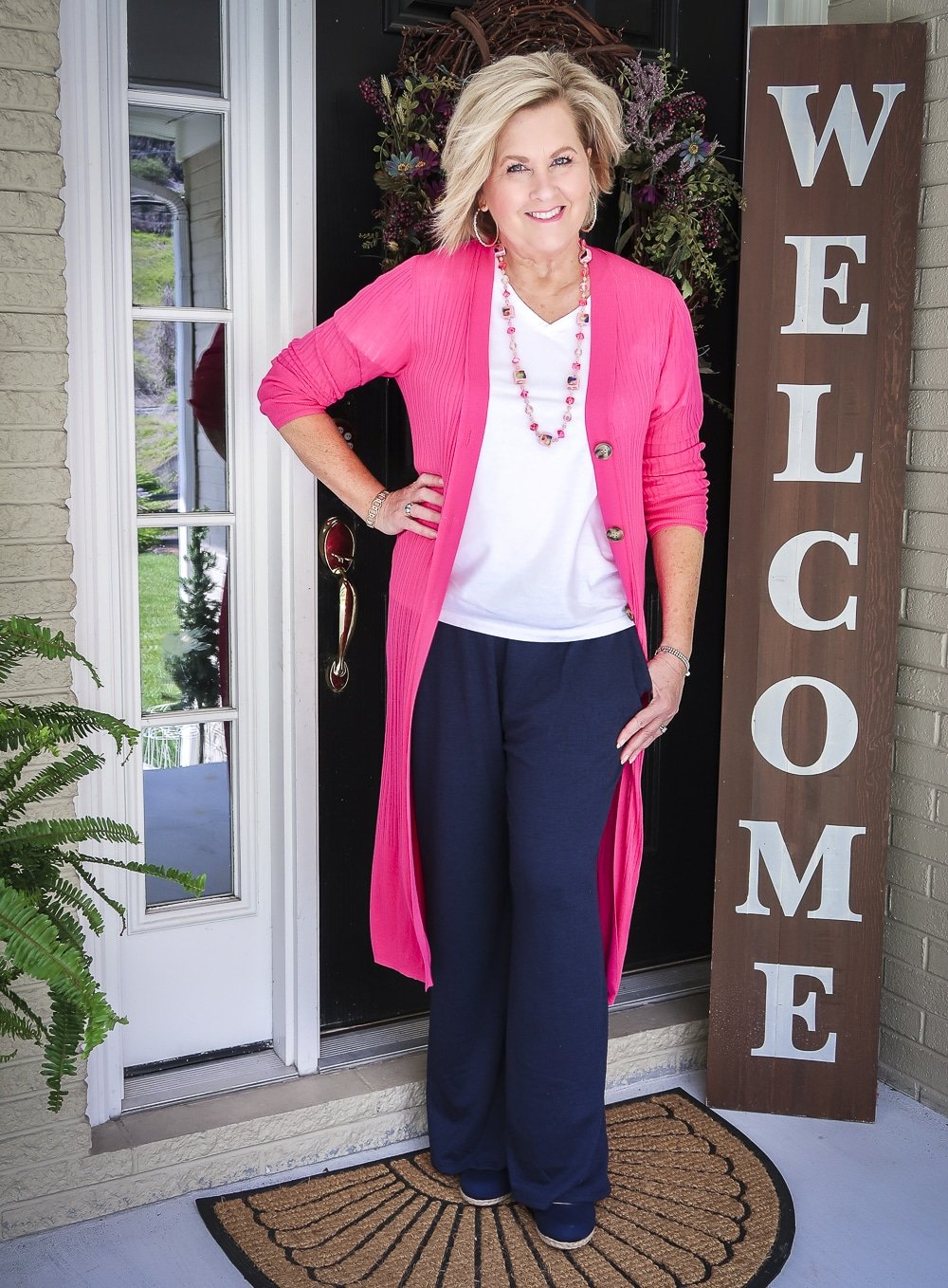 Fashion Blogger 50 Is Not Old wearing a hot pink duster cardigan with a white v-neck t-shirt, vintage jewelry, and navy lounge pants