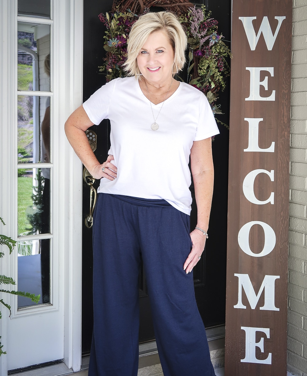 Fashion Blogger 50 Is Not Old wearing a white v-neck t-shirt, and navy lounge pants