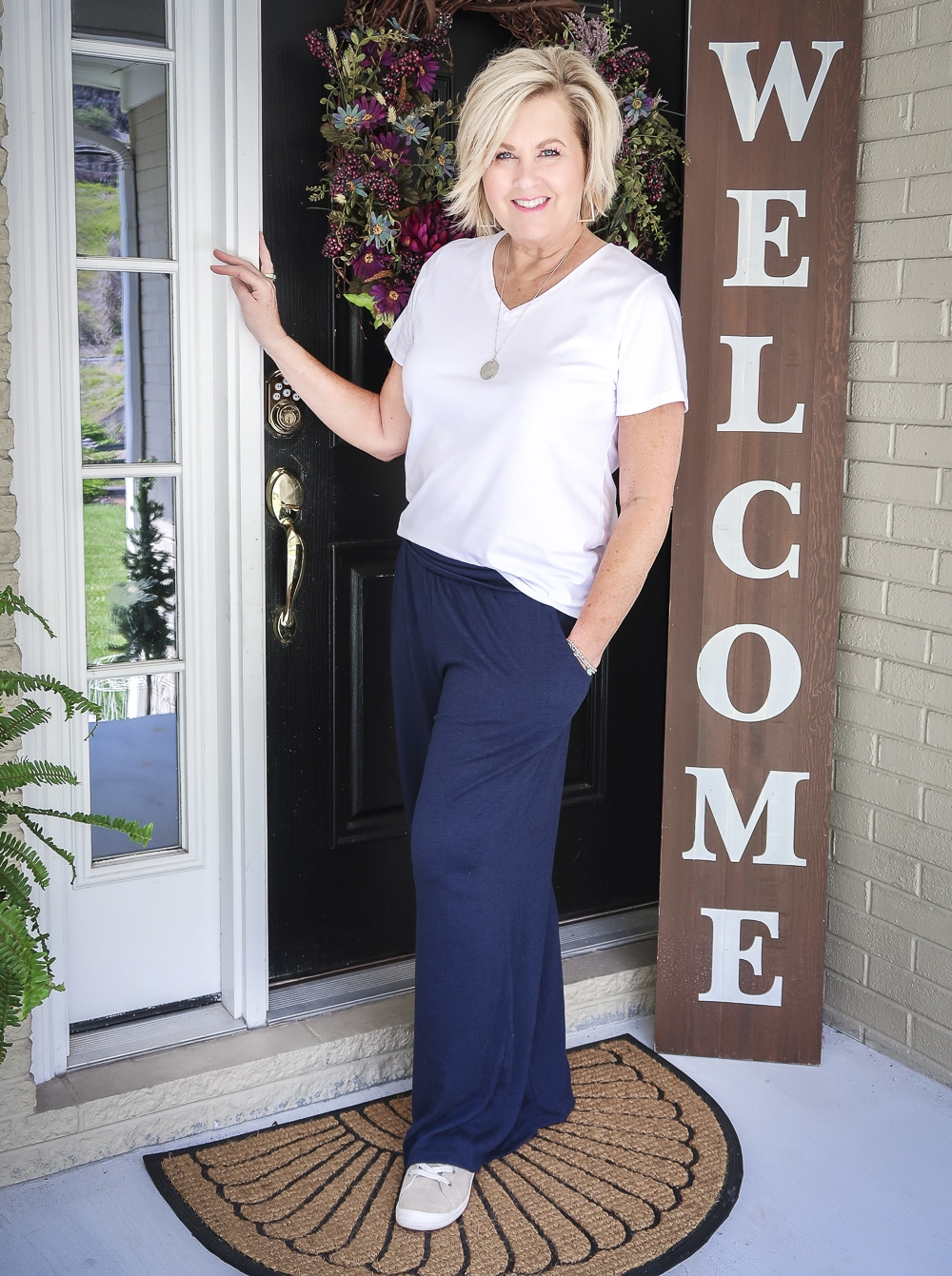 Fashion Blogger 50 Is Not Old wearing a white t-shirt, and navy lounge pants