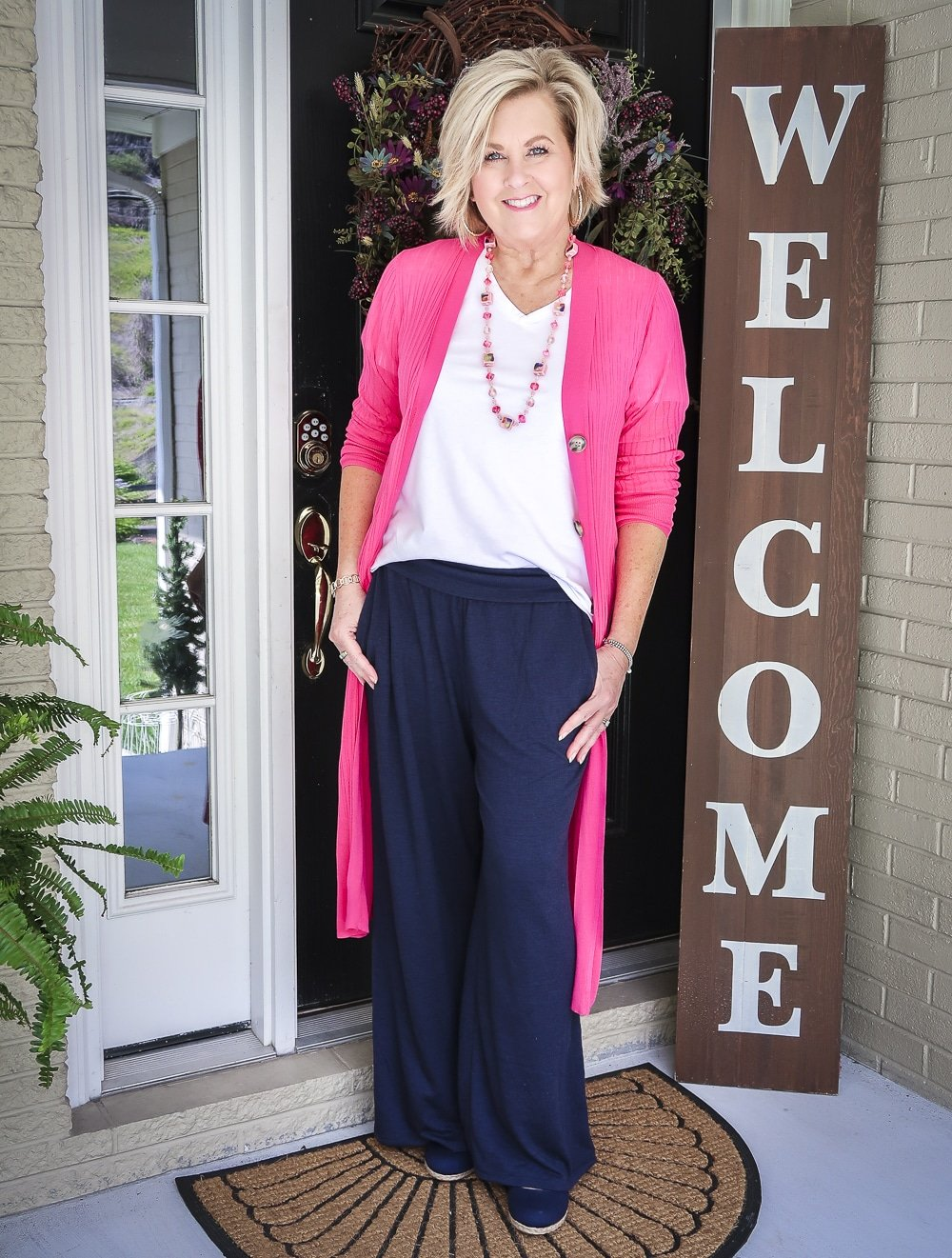 Fashion Blogger 50 Is Not Old wearing a hot pink cardigan with a white v-neck t-shirt, and navy lounge pants