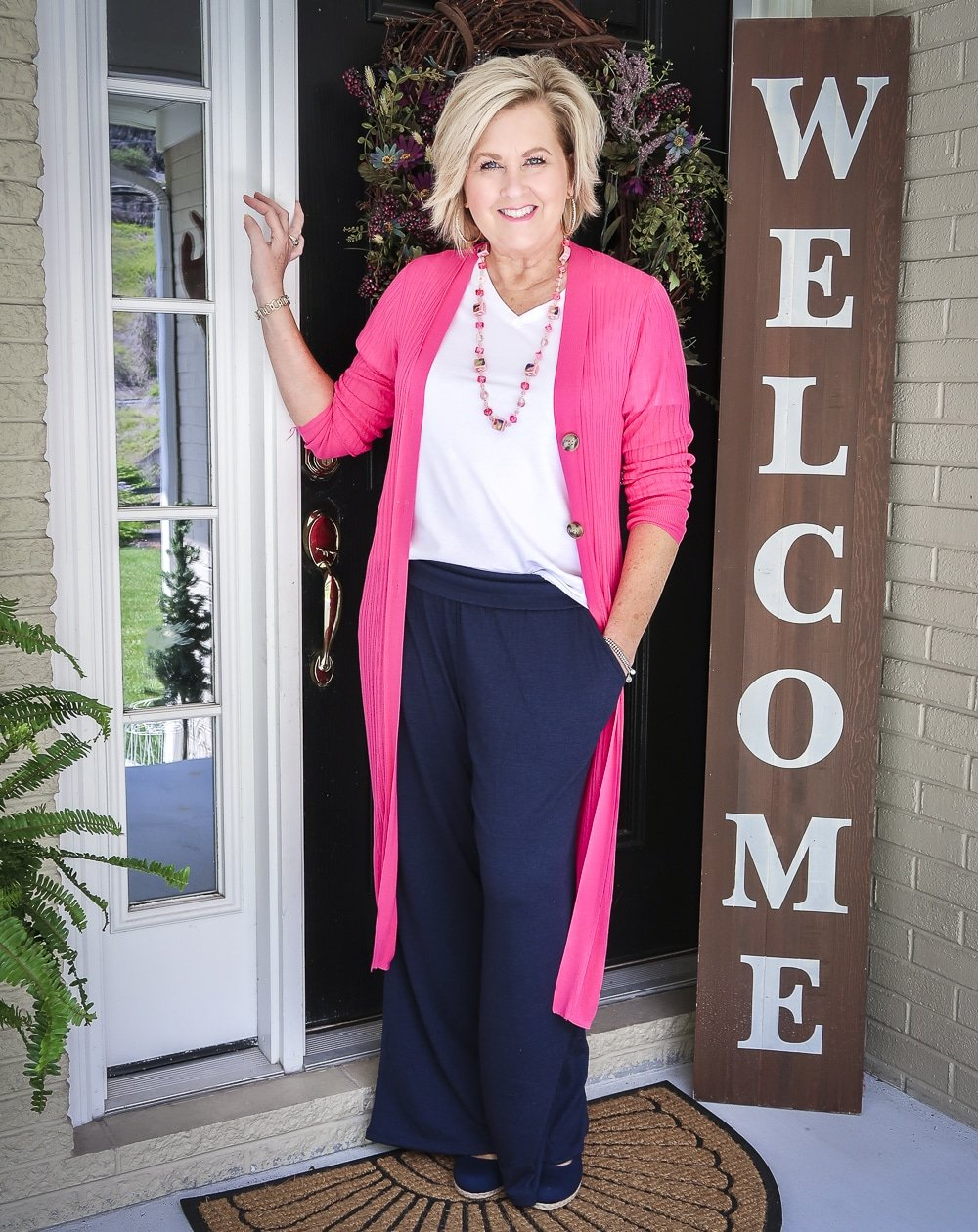 Fashion Blogger 50 Is Not Old wearing a hot pink duster cardigan with a white v-neck t-shirt, and navy lounge pants