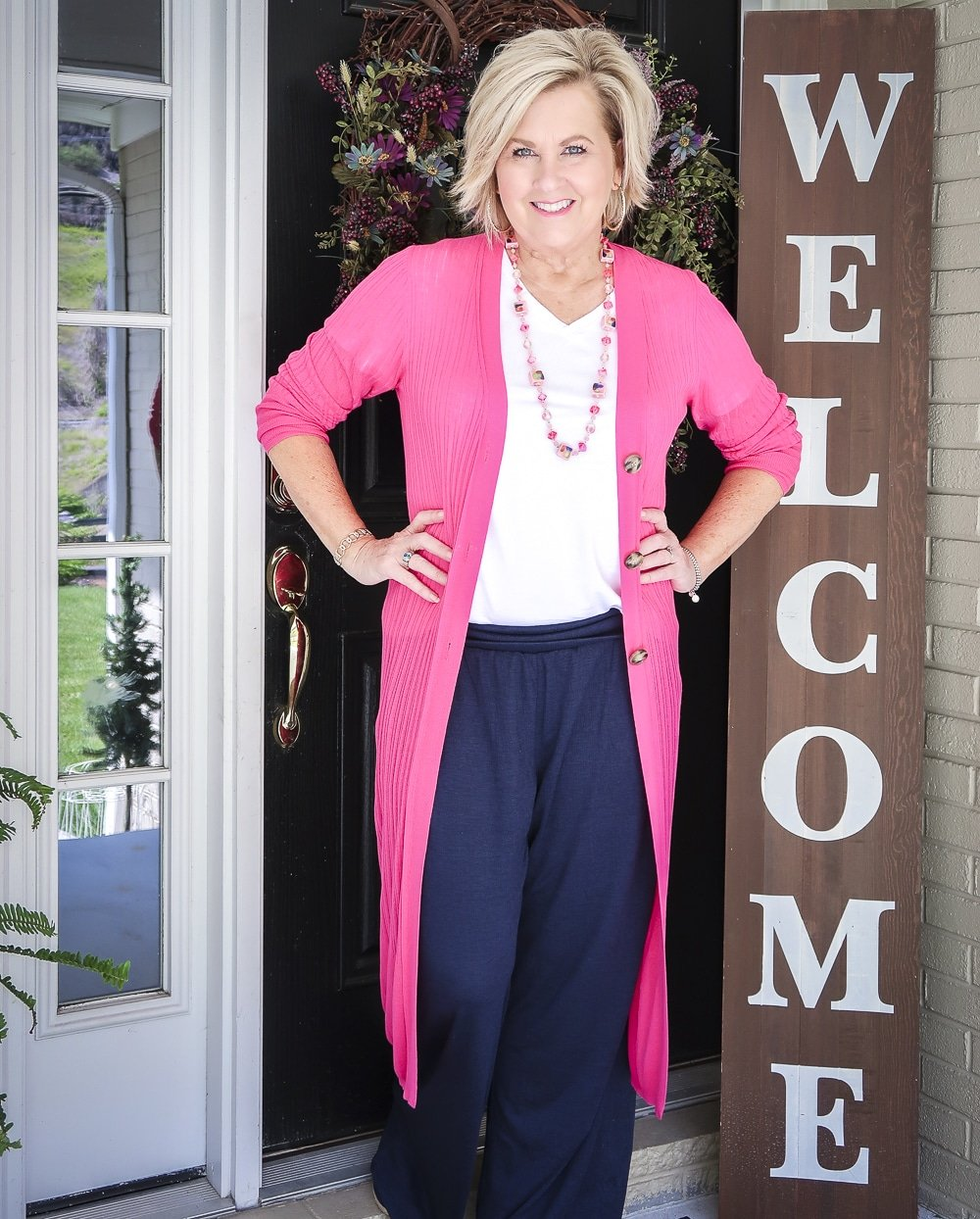 Fashion Blogger 50 Is Not Old wearing a hot pink duster cardigan with a white v-neck t-shirt