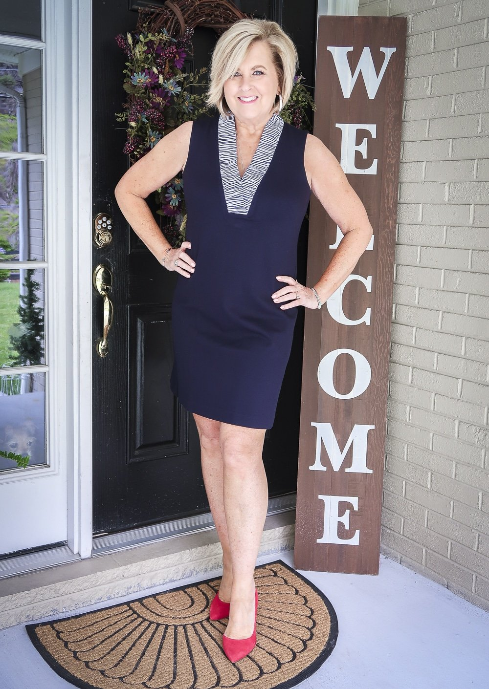 Fashion Blogger 50 Is Not Old is celebrating turning 60 with a navy sheath dress with a striped ruffled neckline from Eliza J and bright red pumps
