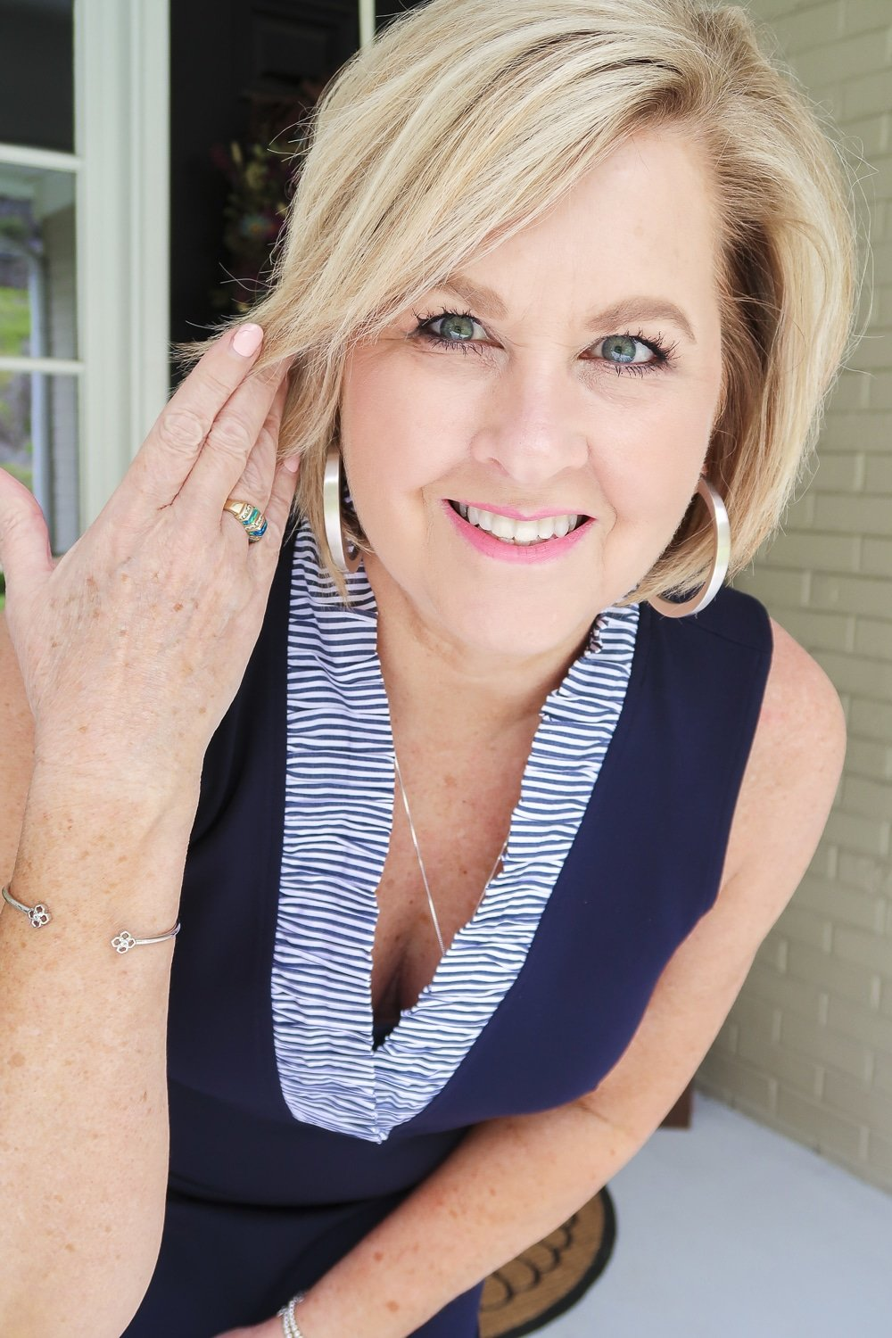 Fashion Blogger 50 Is Not Old is celebrating turning 60 with a navy sheath dress with a striped ruffled neckline and silver jewelry from Kendra Scott