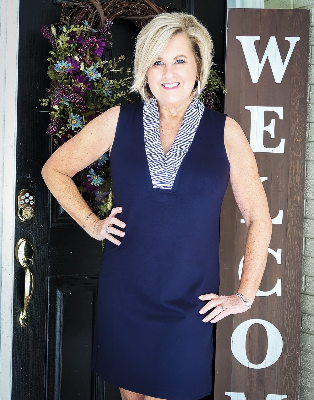 Fashion Blogger 50 Is Not Old is celebrating turning 60 with a navy sheath dress with a striped ruffled neckline