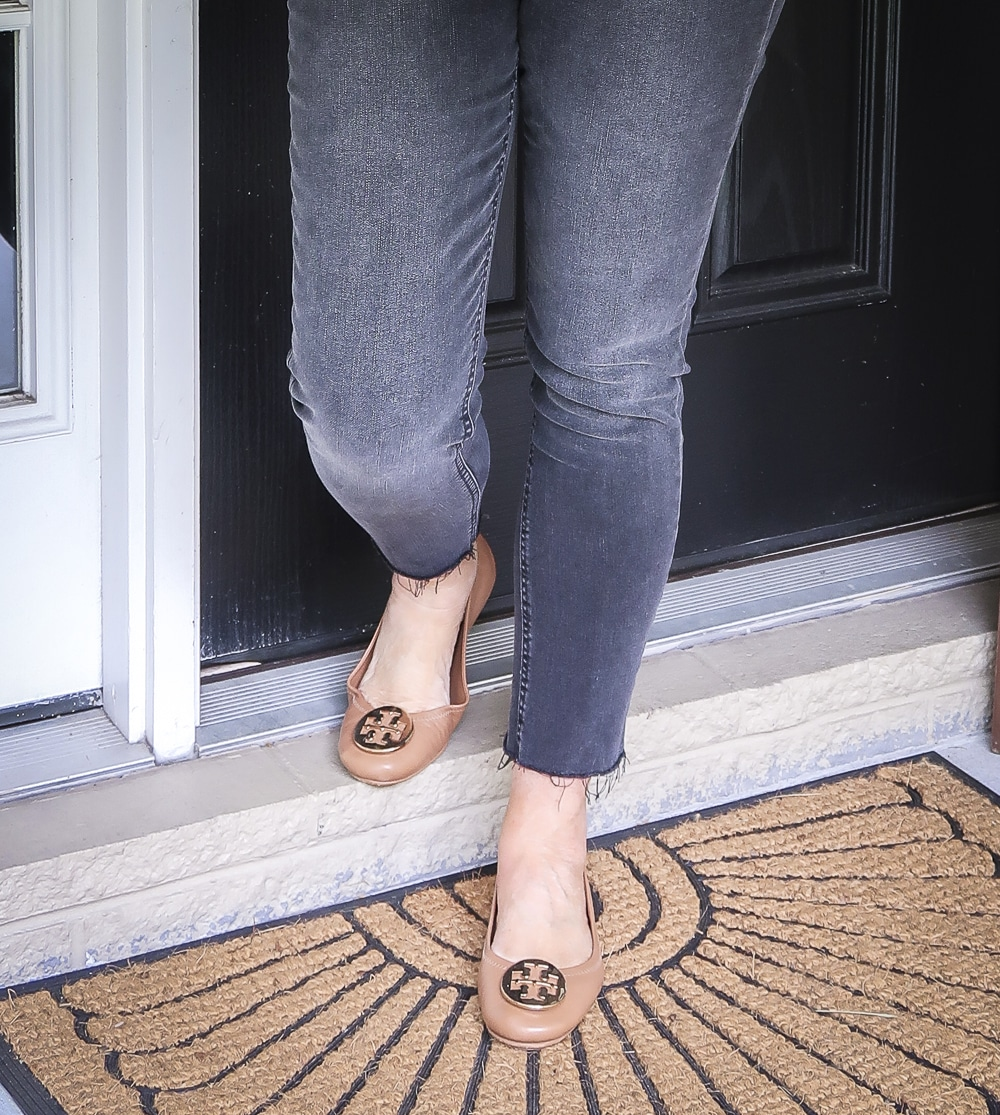 Fashion Blogger 50 Is Not Old wearing faded black jeans and brown ballet flats from Tory Burch