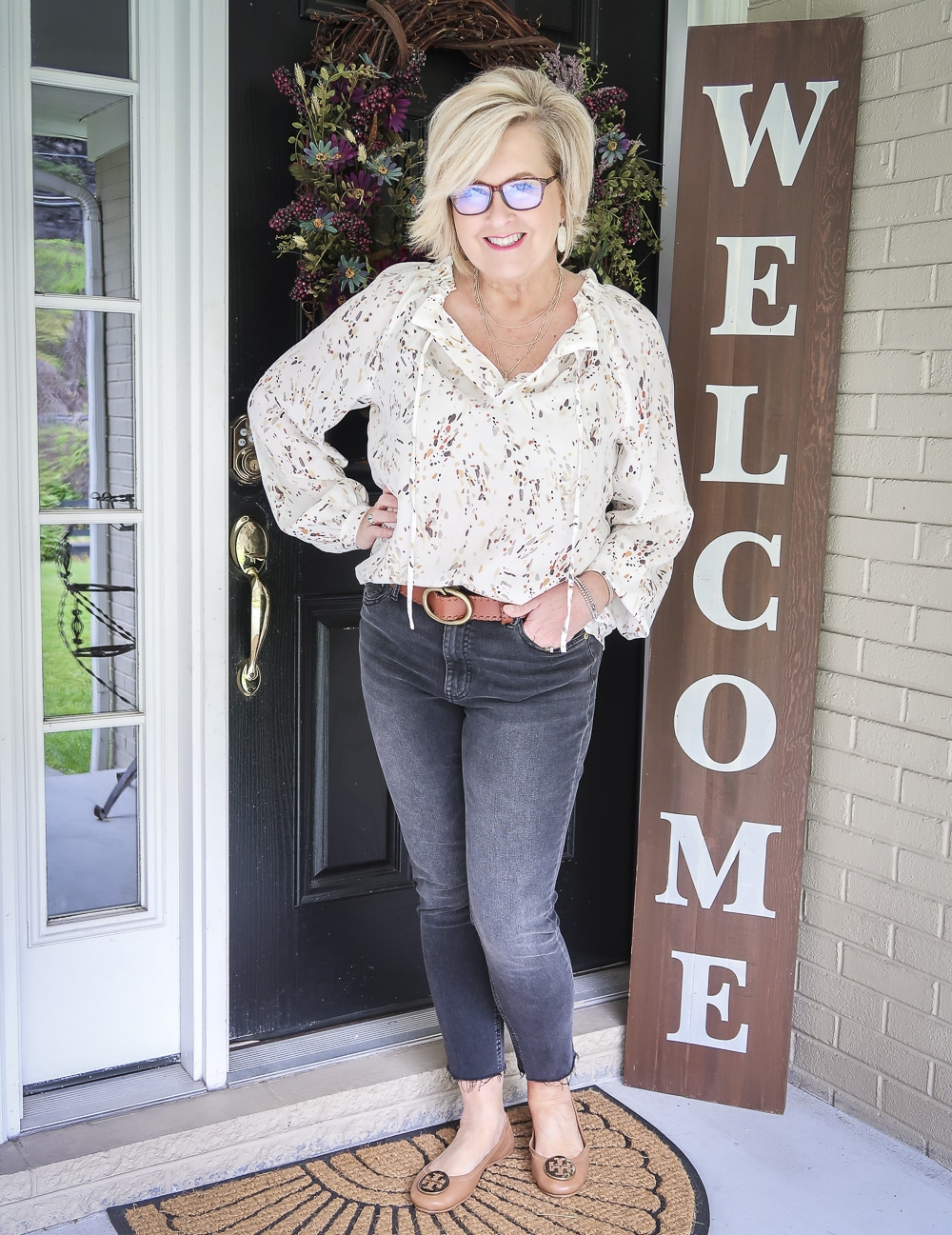 Fashion Blogger 50 Is Not Old wearing a bishop sleeve blouse and faded black jeans with a brown belt and brown ballet flats