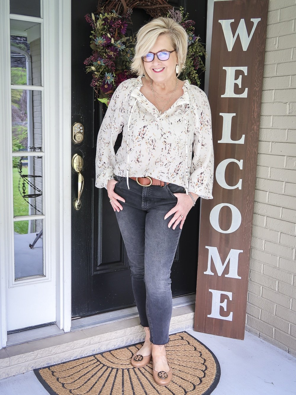Fashion Blogger 50 Is Not Old wearing a bishop sleeve blouse and faded black jeans with a brown belt and ballet flats from Tory Burch