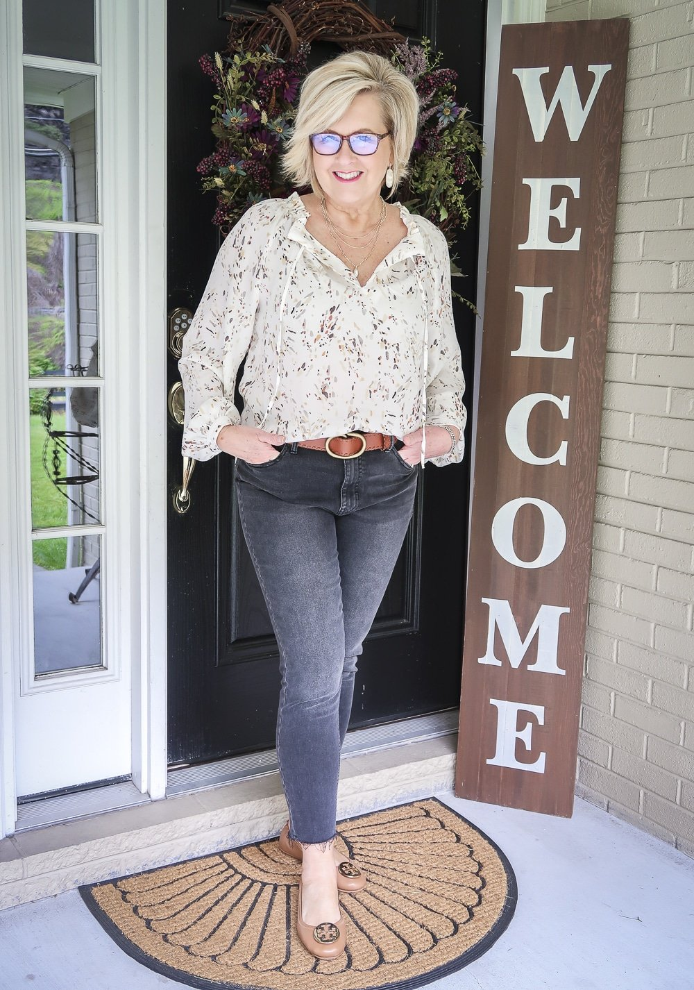 Fashion Blogger 50 Is Not Old wearing a bishop sleeve blouse and faded black jeans and brown ballet flats from Tory Burch
