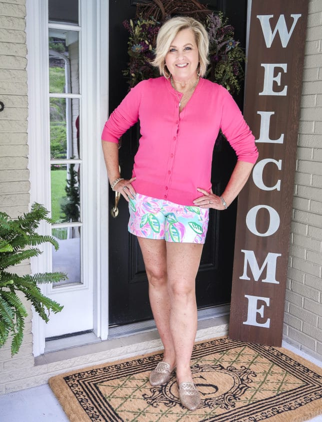 Fashion Blogger 50 Is Not Old is wearing a hot pink sweater with Lily Pulitzer shorts and gold mules