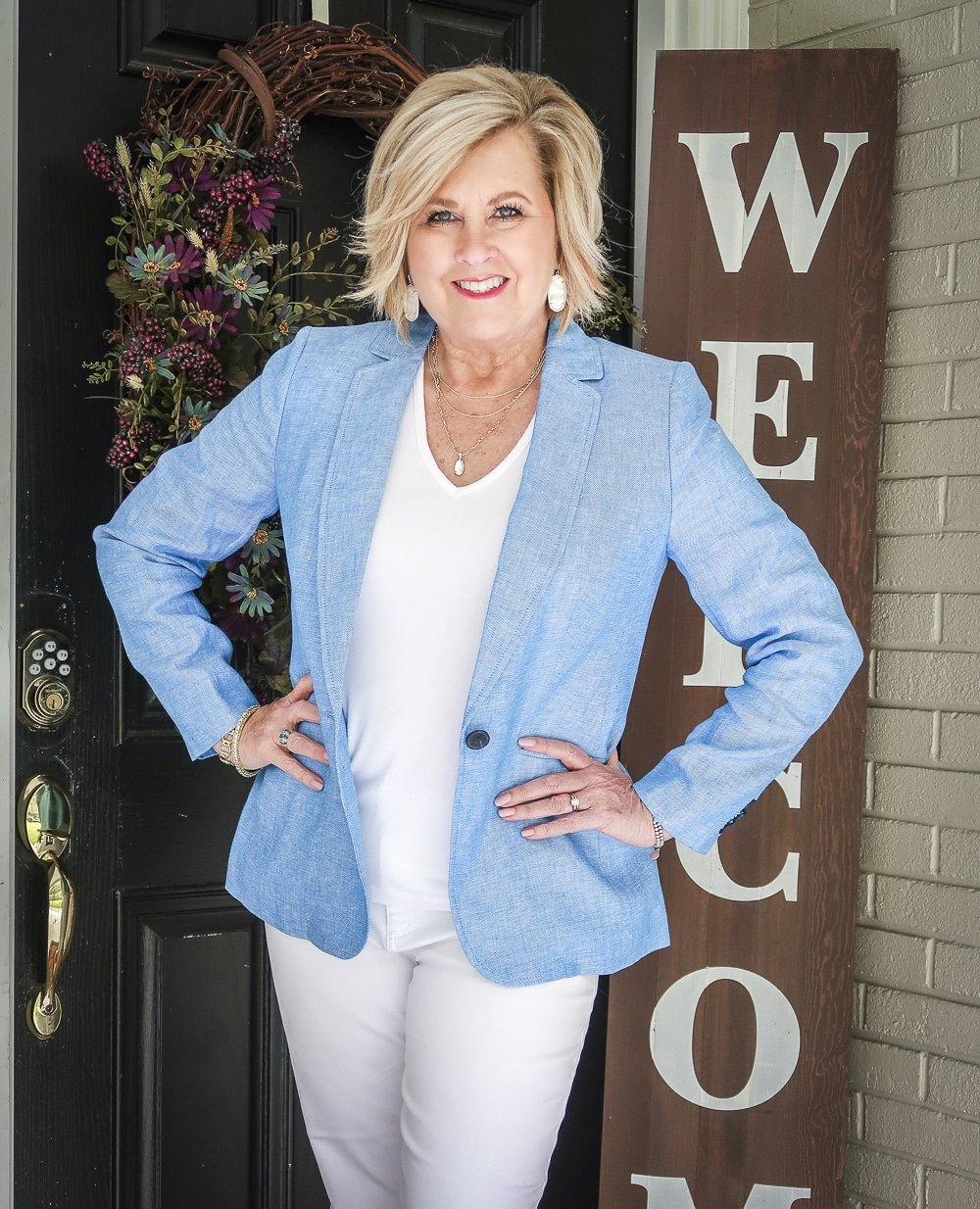 Fashion Blogger 50 Is Not Old is wearing an all white outfit with a blue linen blazer from Talbots and gold jewelry from Kendra Scott