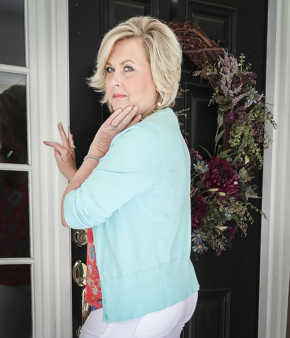 Fashion Blogger 50 Is Not Old is wearing a red ruffled cami and a light turquoise cardigan