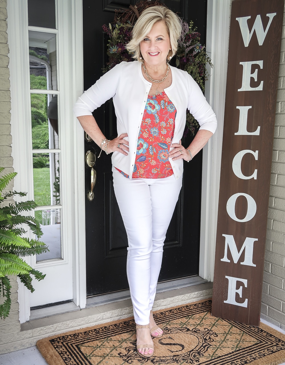Fashion Blogger 50 Is Not Old is wearing a red ruffled cami with white jeggings and a white cardigan