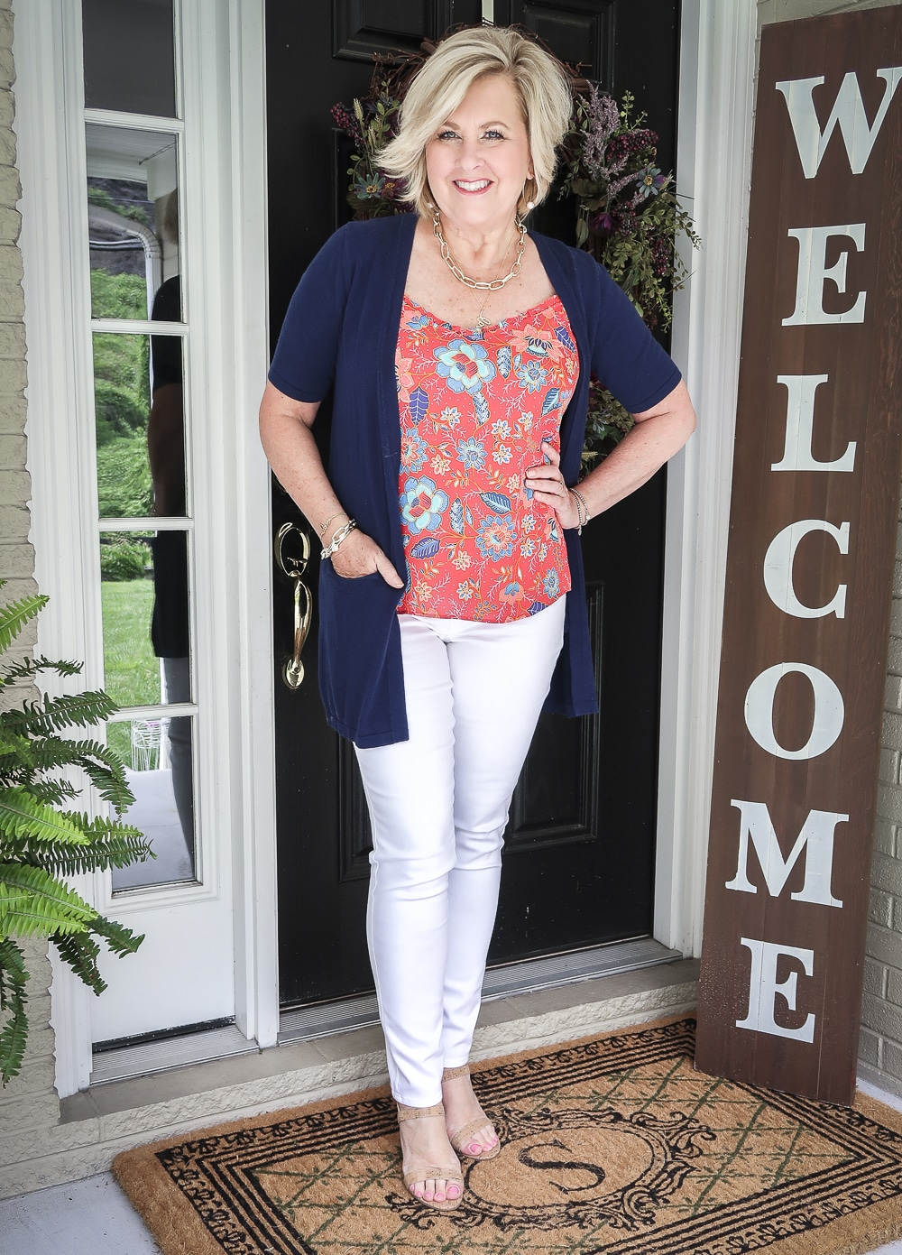 Fashion Blogger 50 Is Not Old is wearing a bright red ruffled cami with white jeggings and a navy short sleeved cardigan