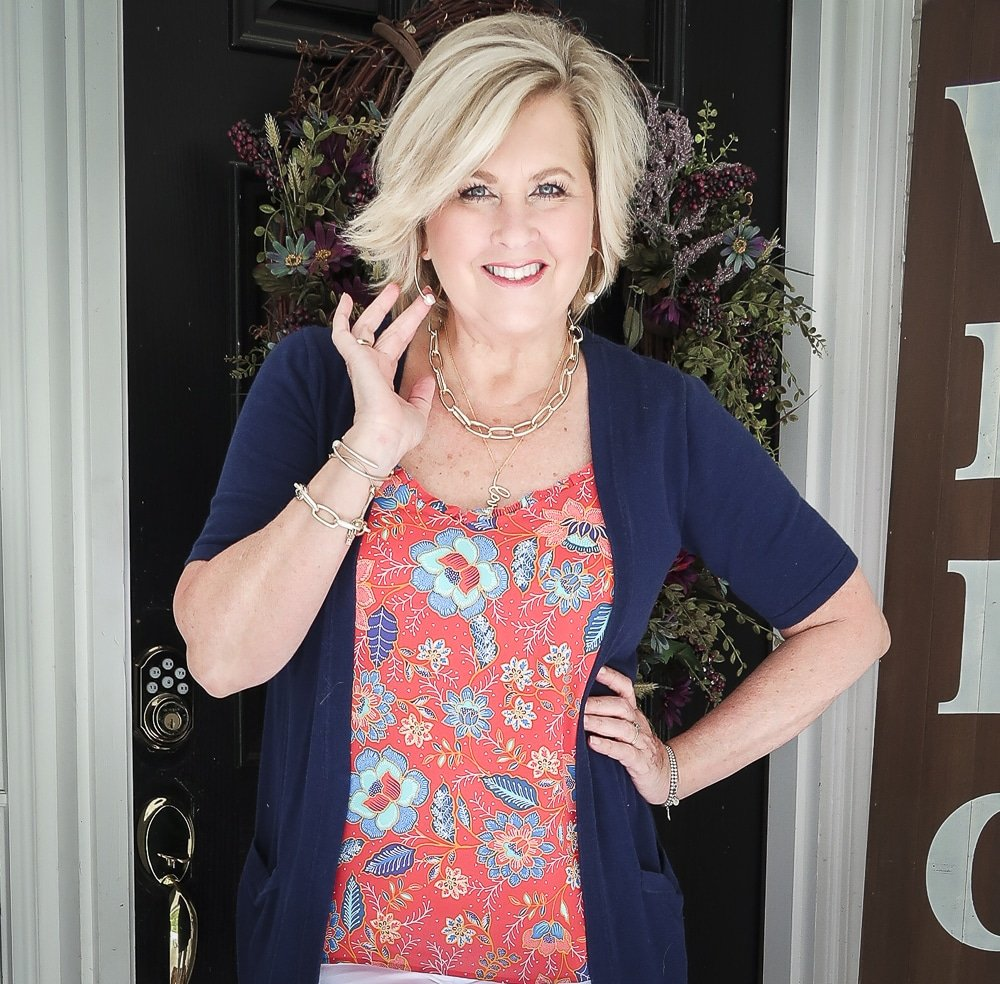 Fashion Blogger 50 Is Not Old is wearing a bright red ruffled cami, a navy short sleeved cardigan, and gold jewelry