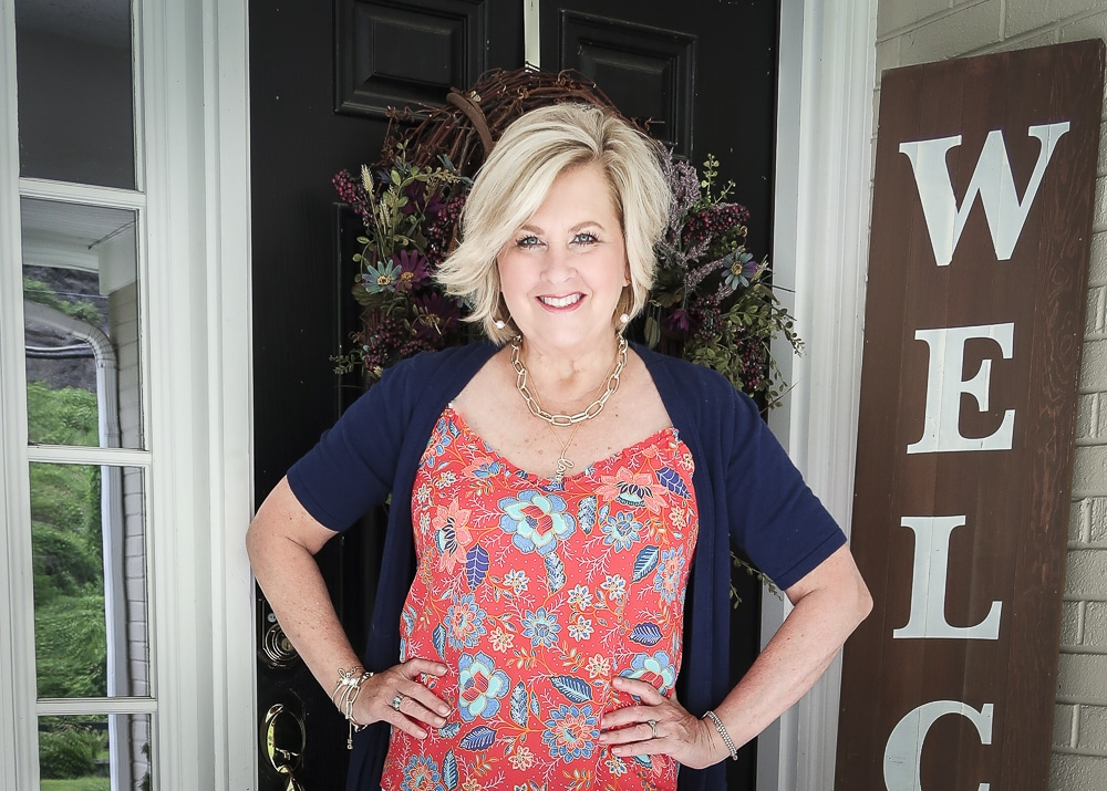 Fashion Blogger 50 Is Not Old is wearing a bright red ruffled cami and a navy short sleeved cardigan