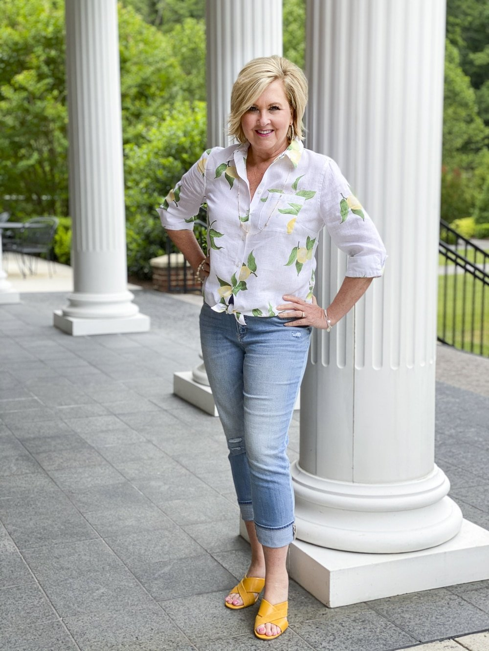 Fashion Blogger 50 Is Not Old is wearing a white button down shirt with yellow lemons, a pair of distressed girlfriend jeans, and mustard yellow block heel sandals