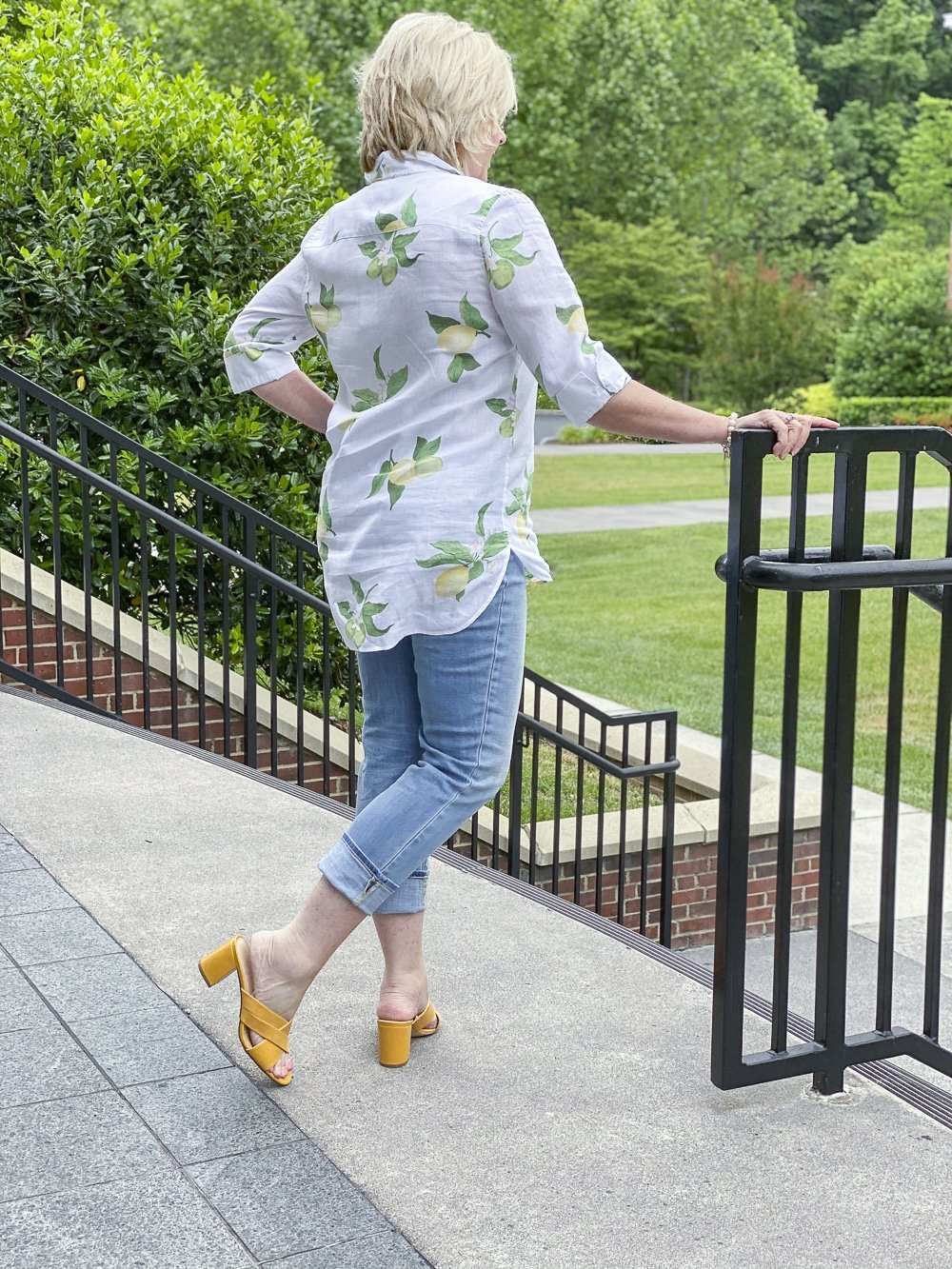 Fashion Blogger 50 Is Not Old is wearing a white button down shirt with yellow lemons, a pair of distressed jeans, and mustard yellow block heel sandals