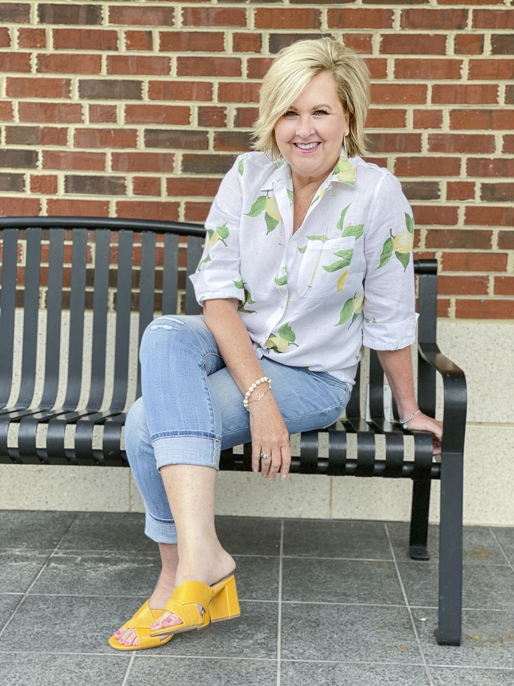 Fashion Blogger 50 Is Not Old is wearing a white button down shirt with yellow lemons, a pair of girlfriend jeans, and mustard yellow block heel sandals