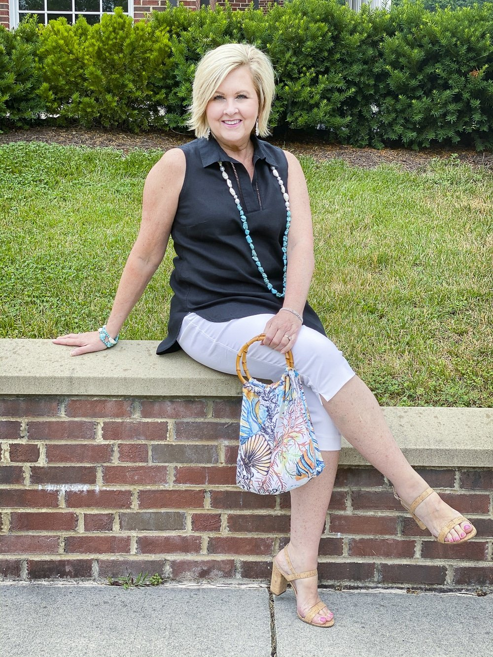 Fashion Blogger 50 Is Not Old is sitting on a brick wall wearing a sleeveless black tunic, a pair of white capris, and a simulated bamboo handled ocean print tote