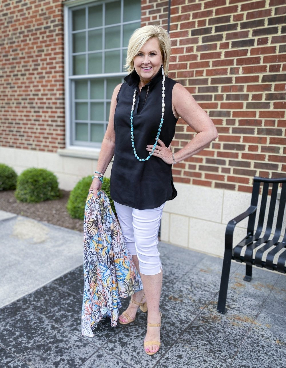 Fashion Blogger 50 Is Not Old is wearing a sleeveless black tunic, a pair of white capris, and an ocean print tote