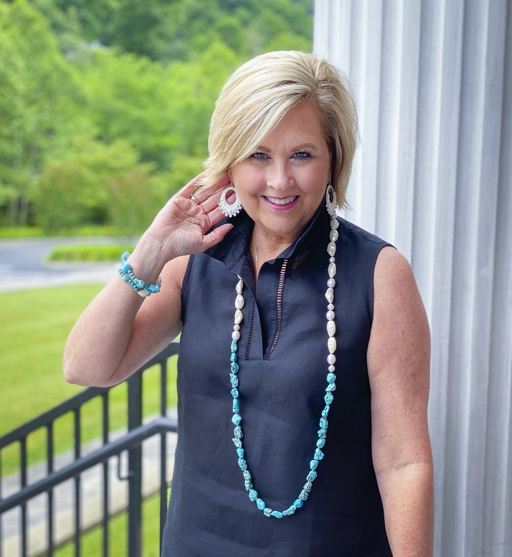 Fashion Blogger 50 Is Not Old is wearing a sleeveless black tunic with freshwater pearl and simulated turquoise jewelry