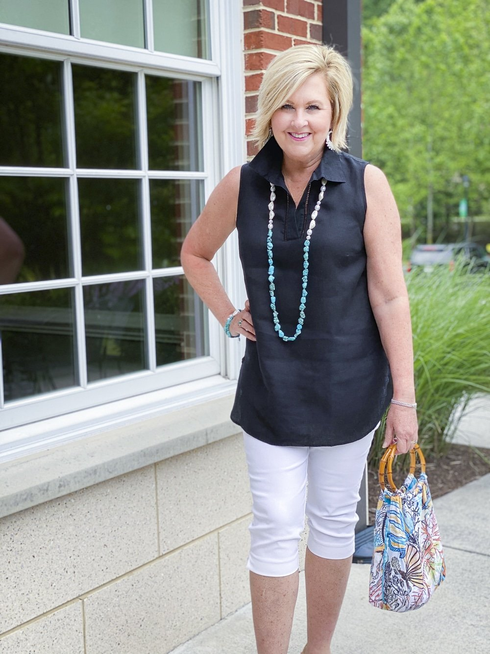 Fashion Blogger 50 Is Not Old is wearing a sleeveless black tunic, a pair of white capris, and a simulated bamboo handled ocean print tote