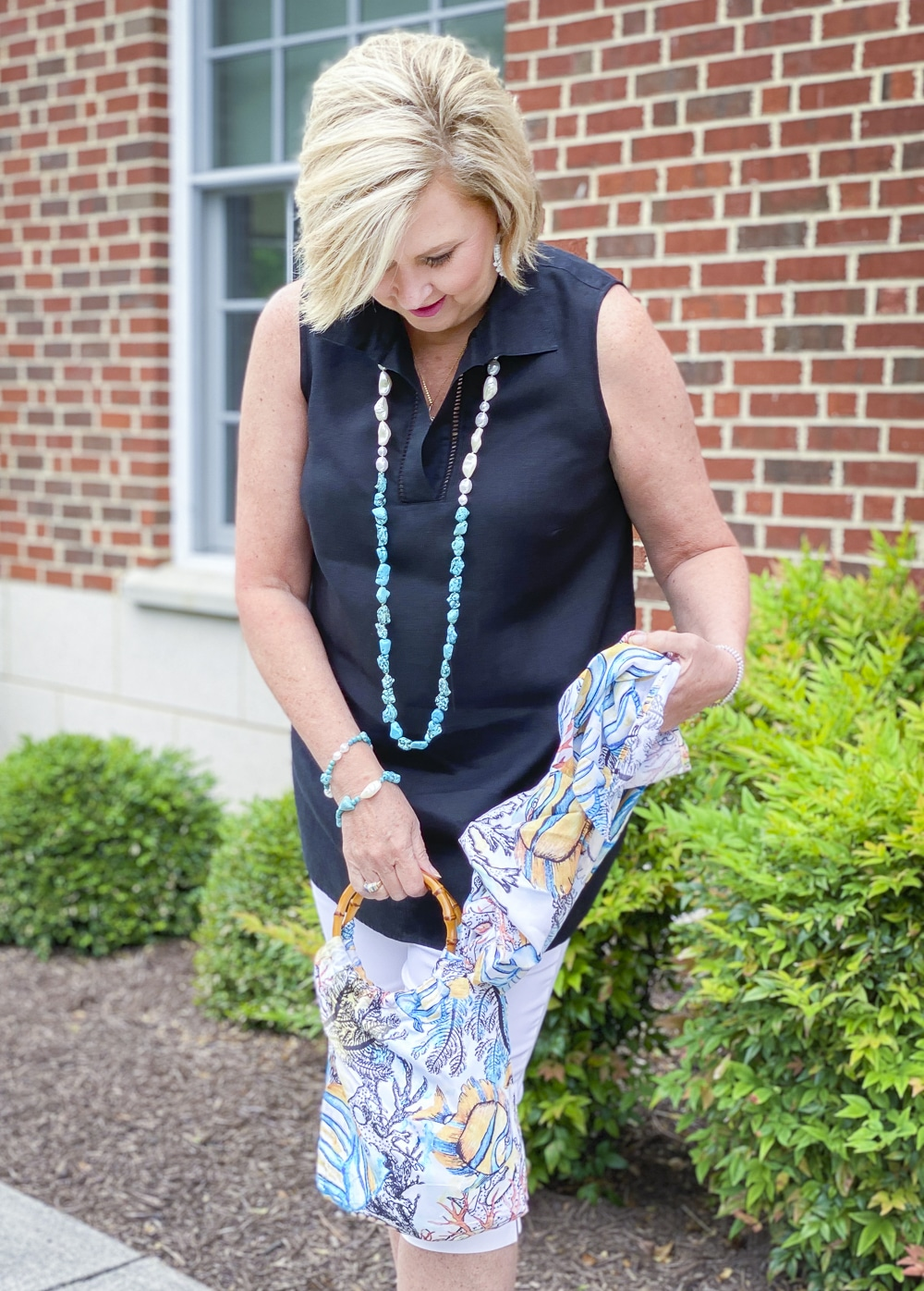 Fashion Blogger 50 Is Not Old is wearing a sleeveless black tunic, a pair of white capris, and a ocean print tote with a scarf