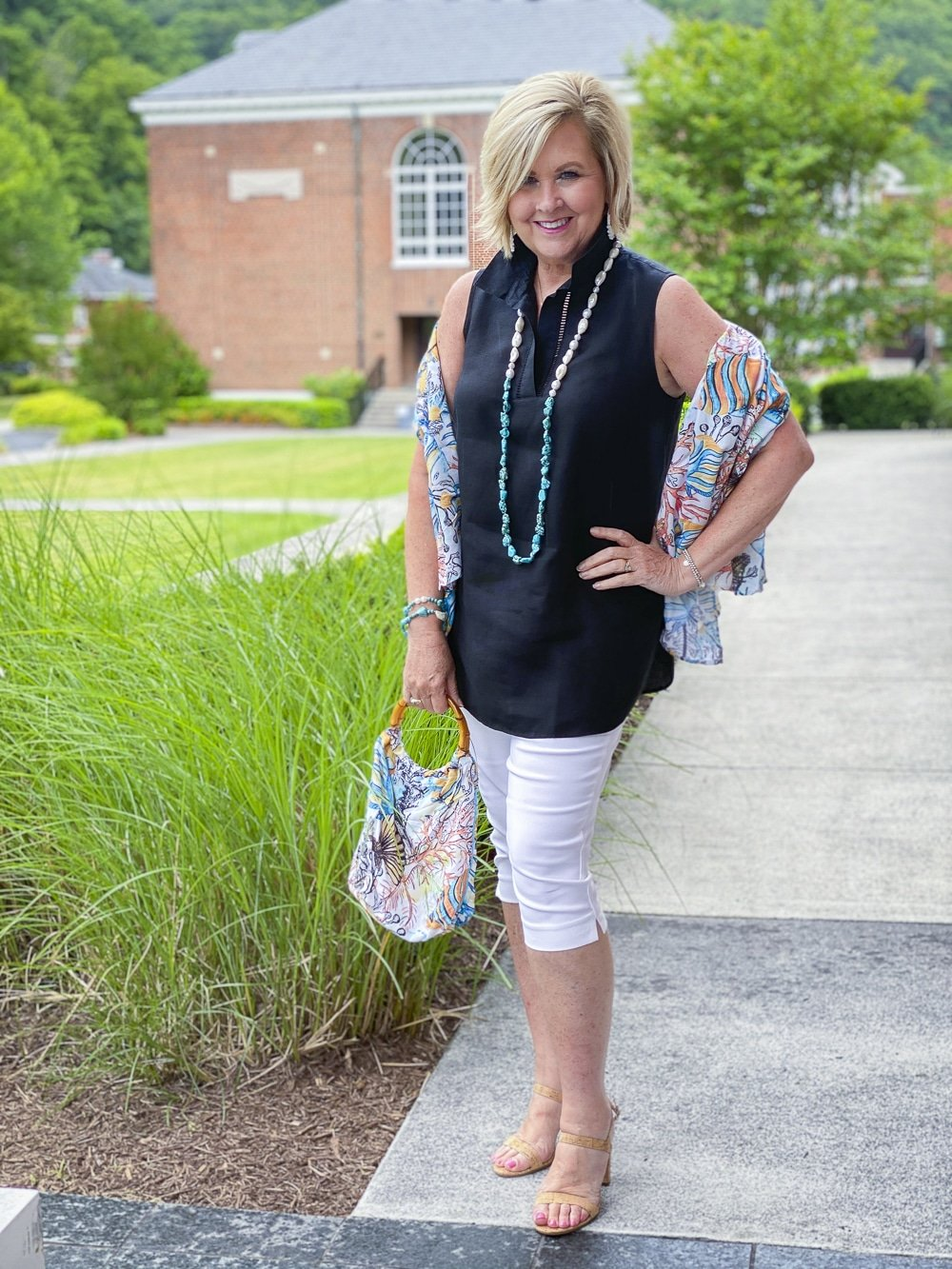 Fashion Blogger 50 Is Not Old is wearing a sleeveless black tunic with an ocean print scarf and a pair of white capris