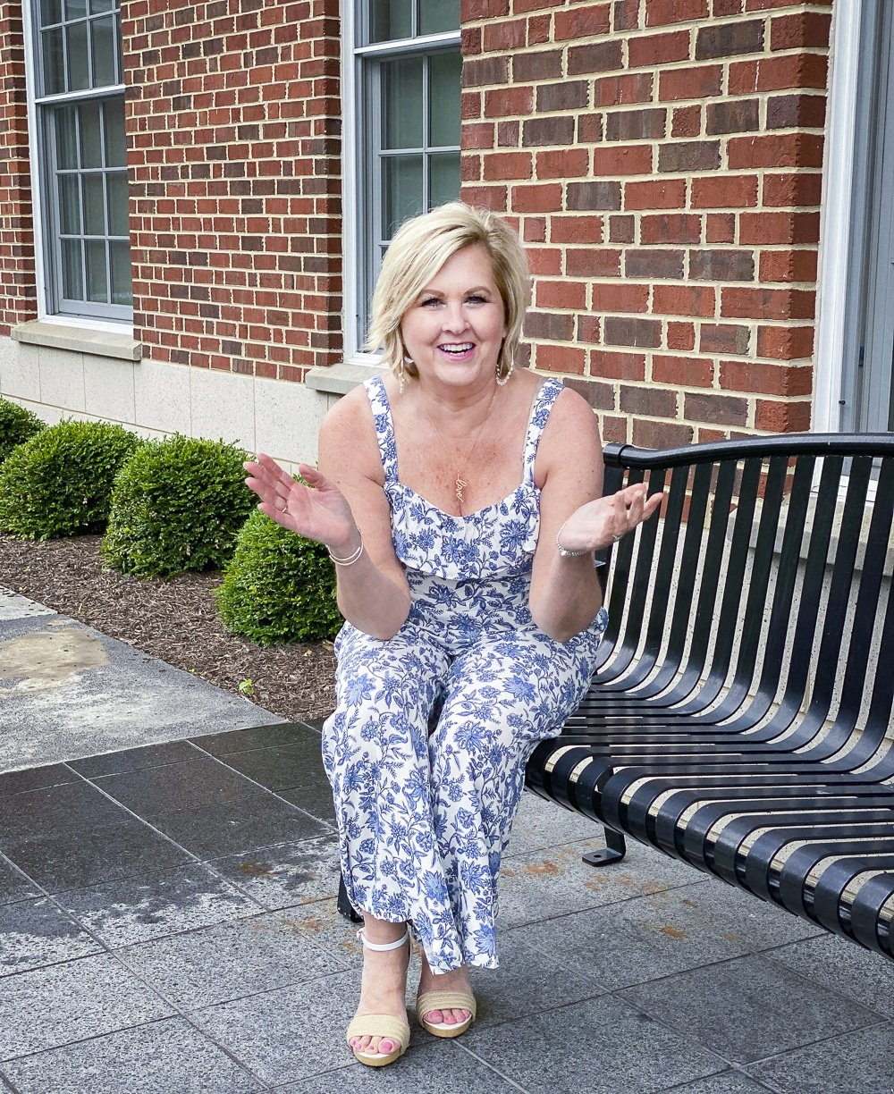 Fashion Blogger 50 Is Not Old is wearing a blue and white jumpsuit, and laughing while sitting on a bench