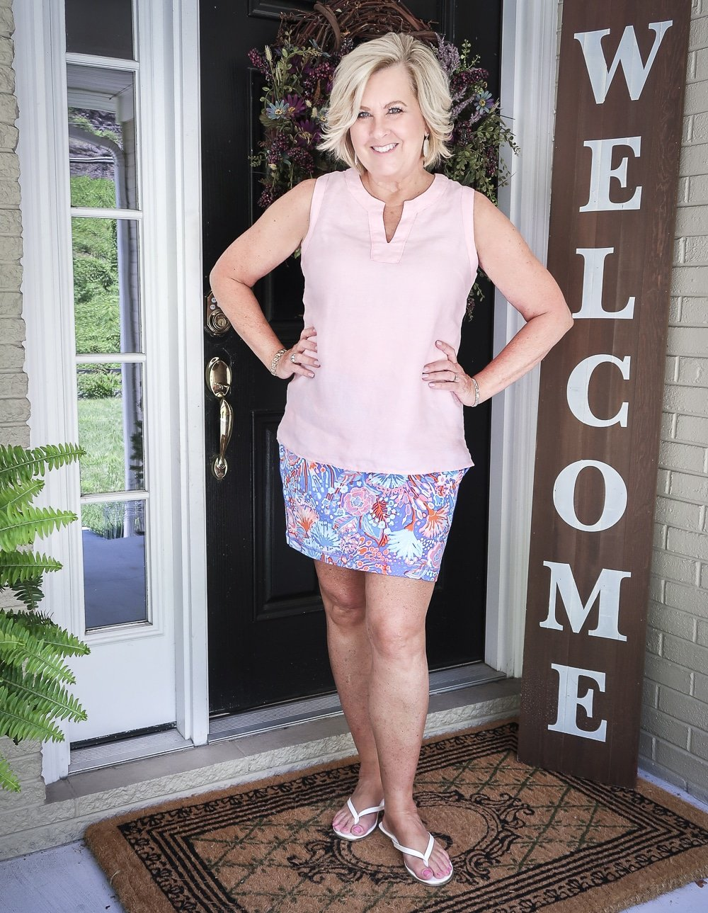 Fashion Blogger 50 Is Not Old is wearing a pale linen v neck top and a colorful yoga skort