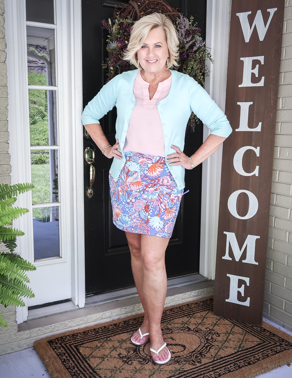 Fashion Blogger 50 Is Not Old is wearing a pale linen v neck top, an aqua colored cardigan, and a colorful yoga skort