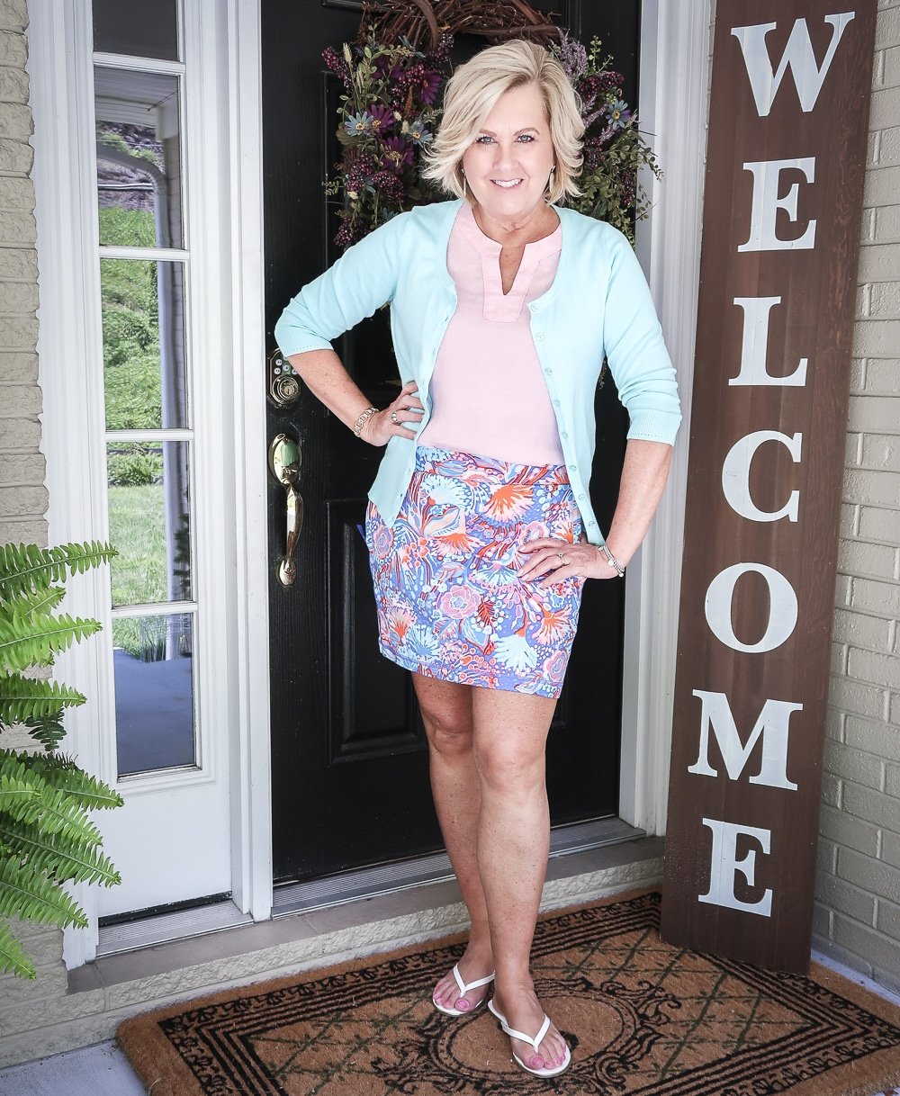 Fashion Blogger 50 Is Not Old is wearing a pale linen v neck top, an aqua colored cardigan, and a colorful skort