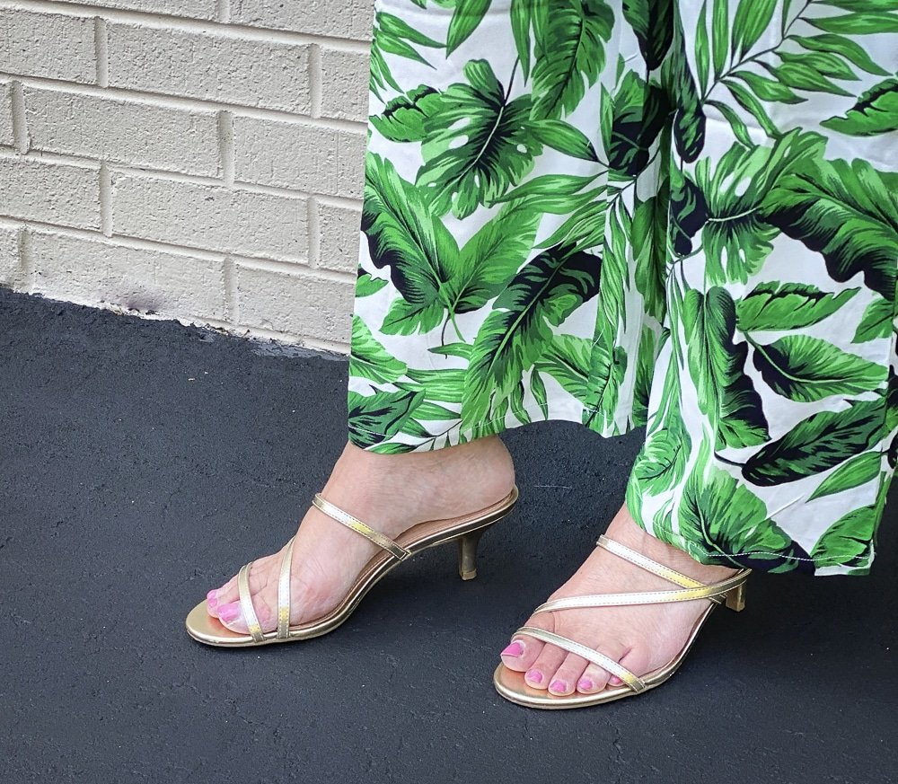 Fashion Blogger 50 Is Not Old is wearing a tropical banana leaf print jumpsuit with pair of gold kitten heels