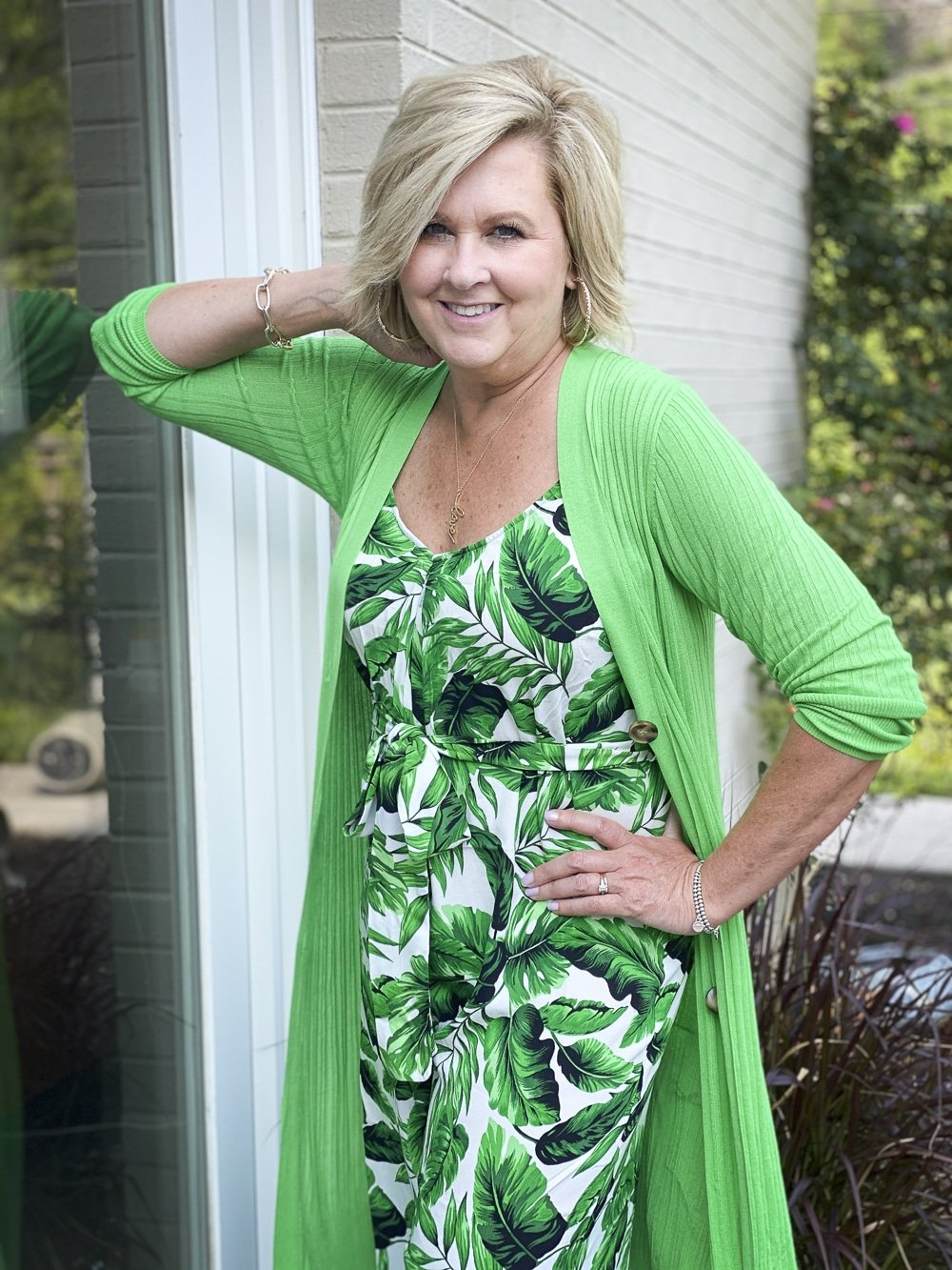 Fashion Blogger 50 Is Not Old is wearing a tropical banana leaf print jumpsuit with a bright green cardigan