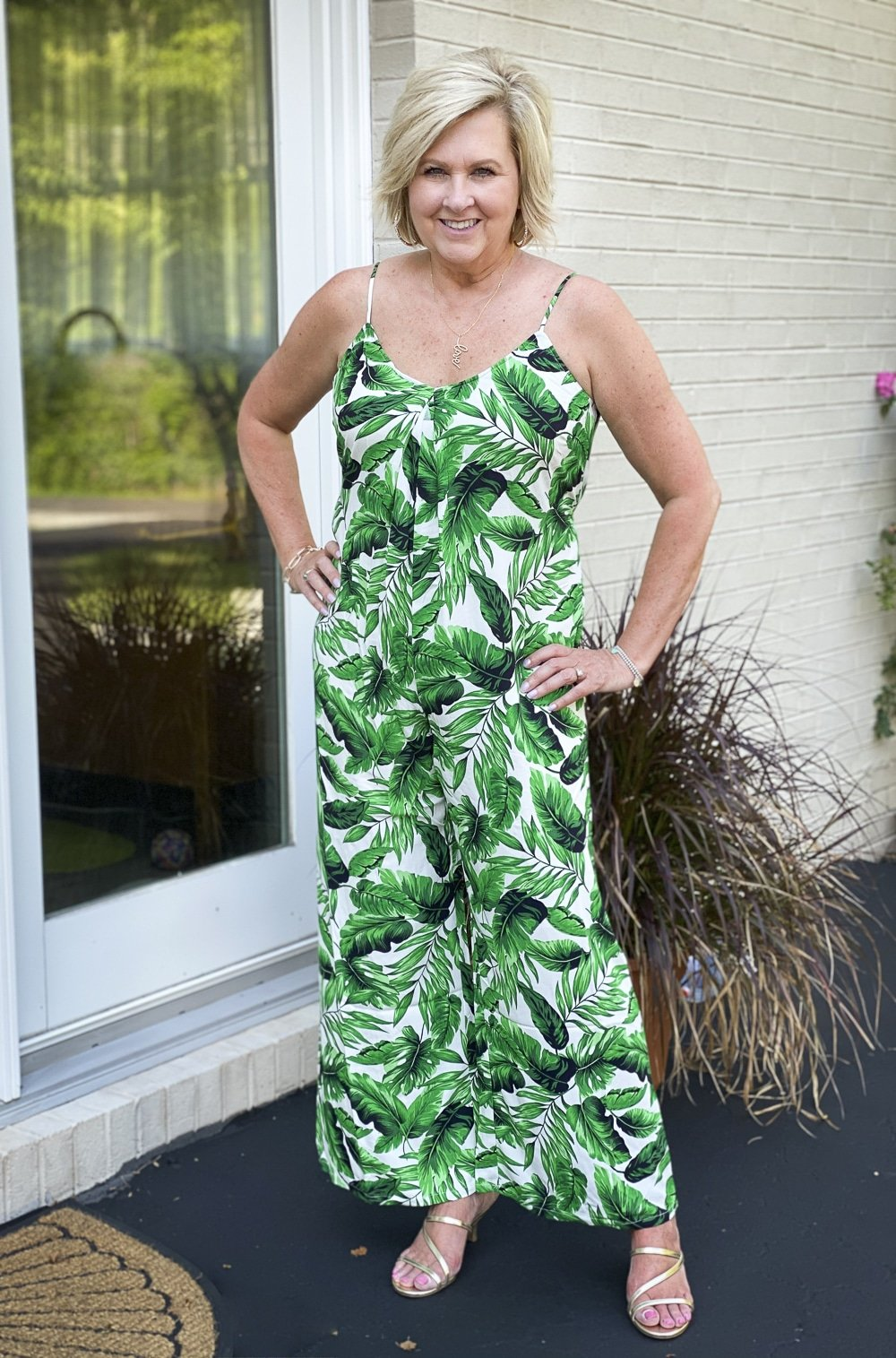Fashion Blogger 50 Is Not Old is wearing a tropical banana leaf print jumpsuit with a pair of gold kitten heels from Walmart